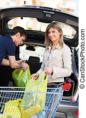 couple doing shopping - young couple arranging shopping bags...