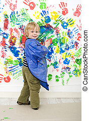 Finger painting - A young boy enjoying himself at...