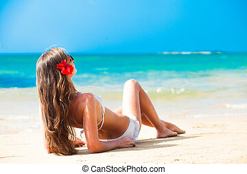 long haired woman with flower in hair in bikini on tropical...