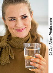 Young housewife drinking glass of water