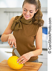 Happy young housewife cutting melon
