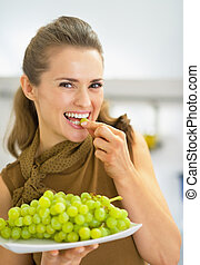 Happy young woman eating grape