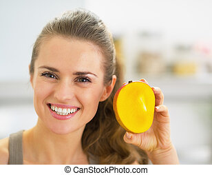 Happy young woman showing mango