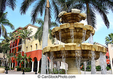 Water Fountain in Front of Colorful Building and Palm Trees