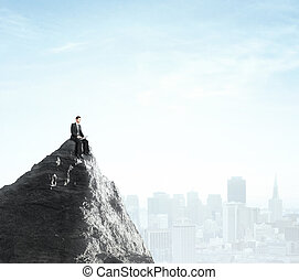 businessman sitting with laptop on top of mountain