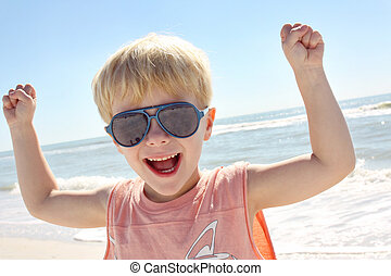 Young Child Flexing Muscles on Beach - a happy young child...