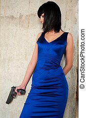 woman with a gun standing near a wall