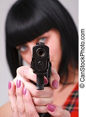 Aiming. Woman with a gun.