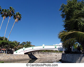 engineered stream with bridge passing over and palm trees in...