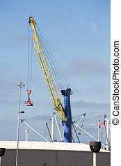 Blue and Yellow Cargo Crane - A blue and yellow crane rests...