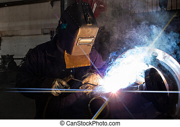 Welder on Pipe - A skilled welder is making a weld on a pipe...