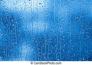 Rainy Window - Raindrops are collecting and streaming down a...