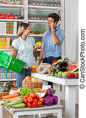 Couple Shopping Vegetables In Supermarket