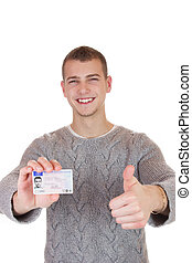 Young man showing his driver license - 16 to 18 year old boy...