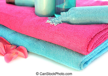 Pink and blue towels with shampoo, solt, cream, body lotion, bath foam, shower gel