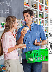 Couple Comparing Cheese At Grocery Store