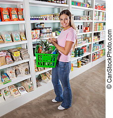 Woman Carrying Shopping Basket In Supermarket