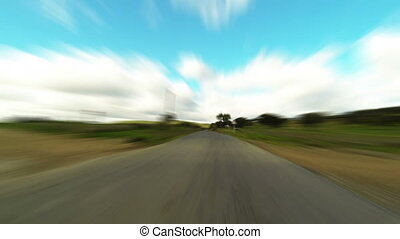 Fast driving car on the road in green fields, blurred...