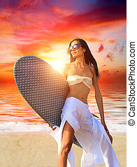 woman with surfboard on the beach at sunset