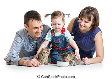 child girl and her parents feeding small kittens