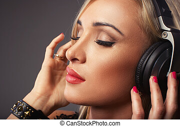 Attractive woman listening music through headphones, eyes...