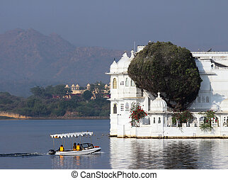 boat and palace on lake in Udaipur