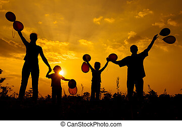 Happy  family dancing with balloons on the  road in the  sunset time. Evening party on the nature