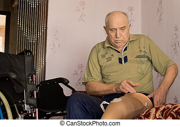 Elderly man fitting a prosthetic leg or artificial limb as...