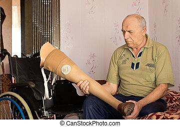Senior man holding a prosthetic leg - Senior disabled man...