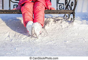 Closeup of little skater's legs standing on winter ice rink