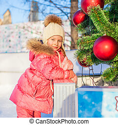 Portrait of adorable little girl at Christmas tree on skating rink