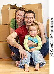 Happy family sitting in on the floor in a new home