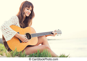Beautiful young woman playing guitar on beach at sunset,...