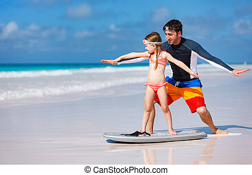 Father and daughter practicing surfing - Father and daughter...
