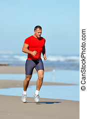 young man jogging on the beach in summer