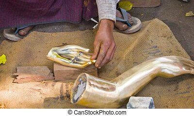 Polishing the parts for bronze statue. Myanmar. Mandalay. metal workshop