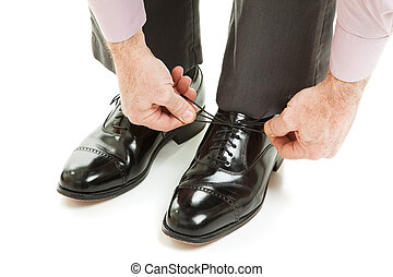 Tying New Shoes - Closeup of a mans hands as he ties his...