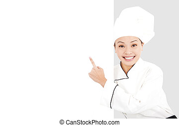 Asian smiling young woman chef pointing with blank board