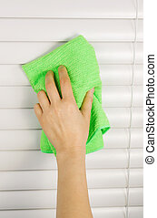 Dusting Window Blinds - Vertical photo of female hand...