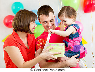kid girl with parents opening gift box