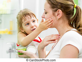 kid daughter putting cream on her mother's face in bathroom