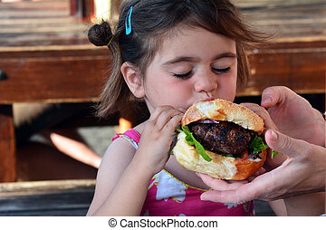 Hamburger - little girl eating big hamburger concept photo
