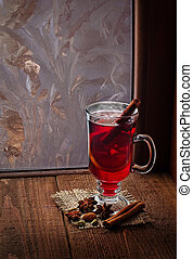 Glass of mulled wine on old wooden table in winter day...