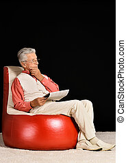 Mature man sitting with newspaper on a black background