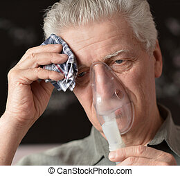 An old man doing inhalation - Close-up of an old man doing...