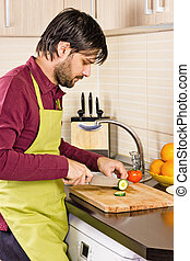 Handsome young man in the kitchen cutting vegetables