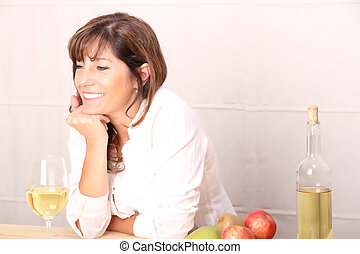Woman with white wine - A beautiful mature woman with a...