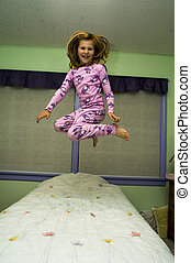 Jumping on a bed - Young girl jumping on a bed in a bedroom...