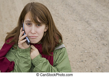 Teenage girl talking on a cell phone - Sad teenage girl on a...