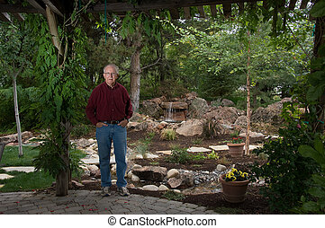 Elderly man standing in his garden - Senior man standing by...